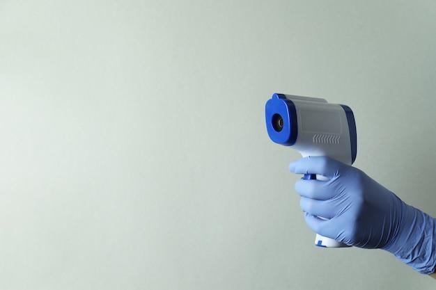Ręka w rękawicy trzymać pistolet termometr, miejsce na tekst