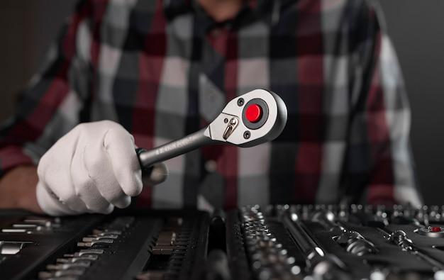 Ręka w rękawicy zbliżenie z metalowym uchwytem grzechotki ze stali nad zestawem narzędzi.