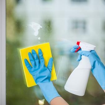 Ręka w rękawiczce myje okno