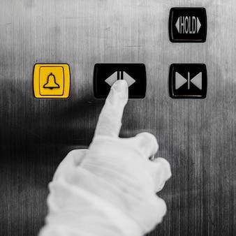 Ręka w rękawiczce naciskająca przycisk windy, aby zapobiec skażeniu koronawirusem