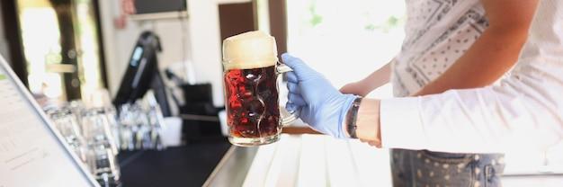 Ręka w rękawiczce przed zimną szklanką z kwasem chlebowym lub piwem