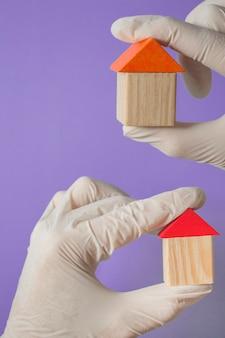 Ręka w rękawiczce trzyma drewniany dom - koncepcja ubezpieczenia zdrowotnego lub baner lekarza rodzinnego, kopia przyprawy