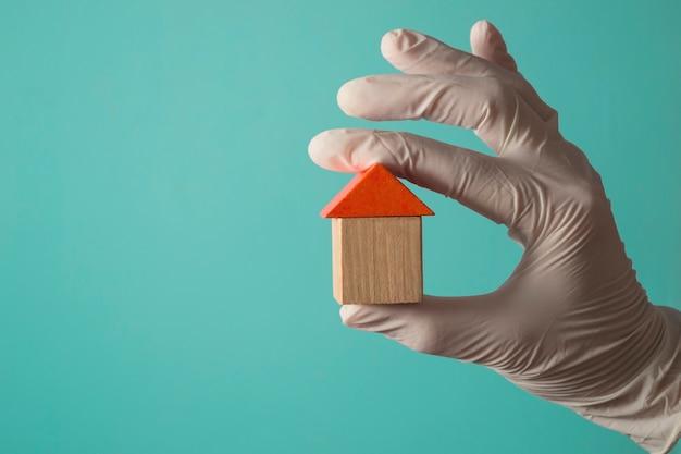 Ręka w rękawiczce trzyma drewniany dom - koncepcja ubezpieczenia zdrowotnego lub lekarza rodzinnego