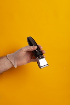 Ręka w rękawiczce trzyma maszynkę do strzyżenia włosów