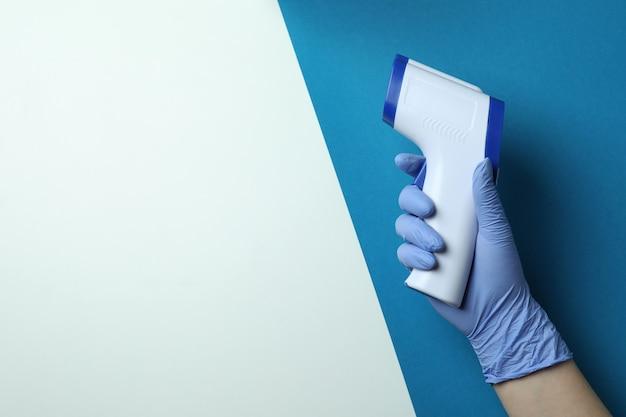 Ręka w rękawiczce trzymaj pistolet termometryczny na dwa tony