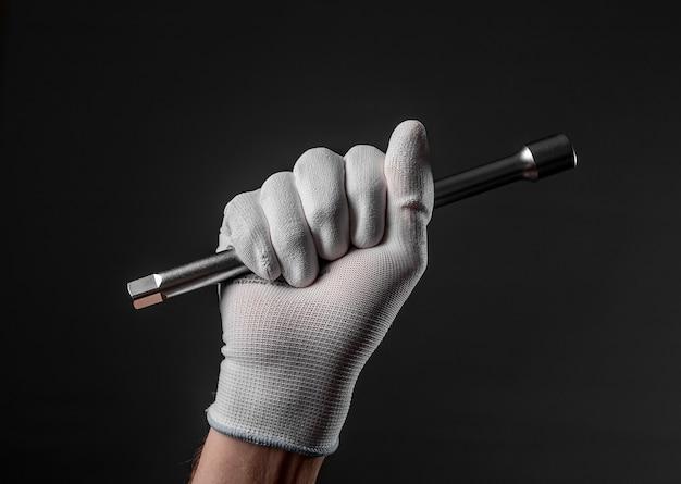 Ręka w rękawiczce z metalowym narzędziem do naprawy samochodu na czarnym tle