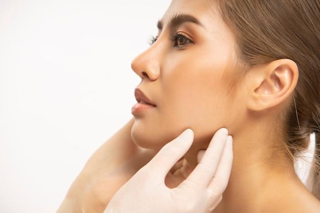 Ręka w rękawiczkach chirurgicznych o pięknej kobiecej twarzy