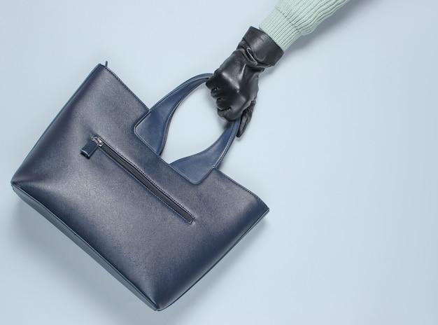 Ręka w rękawiczkach trzyma skórzaną torebkę na szarym papierze. widok z góry. płaski układ