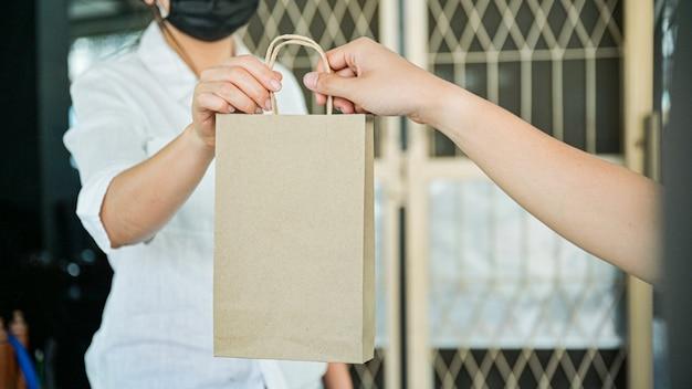 Ręka w rękę zamów produkty i żywność dostarczane do domu, aby zapobiec przenoszeniu koronawirusa lub covid-19.