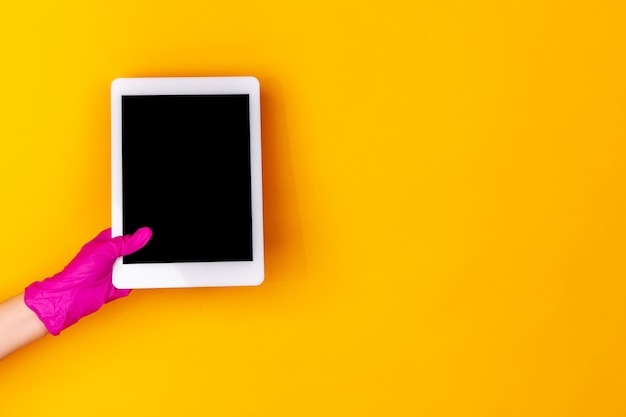 Ręka w różowe gumowe rękawice ochronne z tabletem na białym tle na żółtym tle studio z lato. gestykulowanie, trzymanie, prezentowanie rzeczy. negatywna przestrzeń dla twojej reklamy. pokazywanie, wskazywanie.