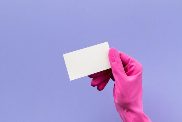 Ręka w różowe rękawiczki gumowe trzymając wizytówkę na fioletowym tle. usługa sprzątania lub makieta sprzątania.