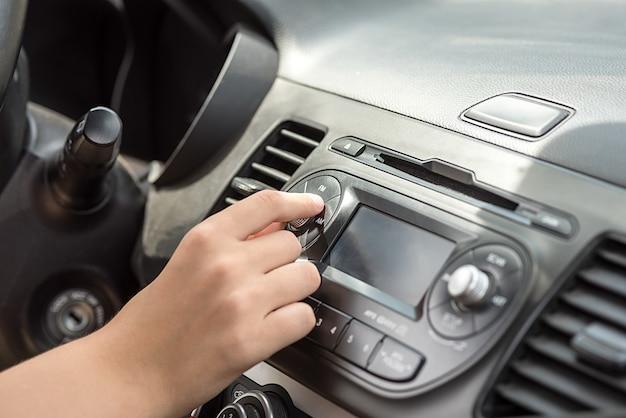 Ręka w samochodzie obraca przycisk głośności. deska rozdzielcza w samochodzie.