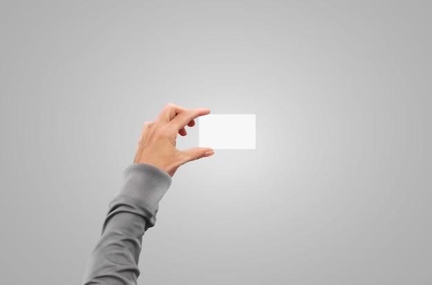 Ręka w swetrze w kurtce swetrowej trzyma wizytówkę