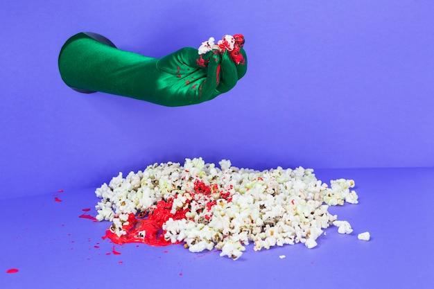Ręka w zielonej rękawiczce gospodarstwa popcorn