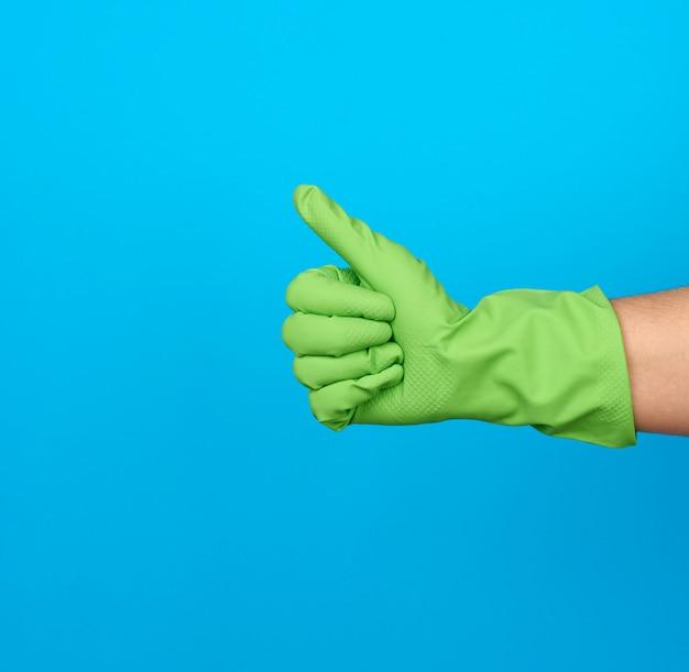 Ręka w zielonych gumowych rękawiczkach ochronnych pokazuje gest
