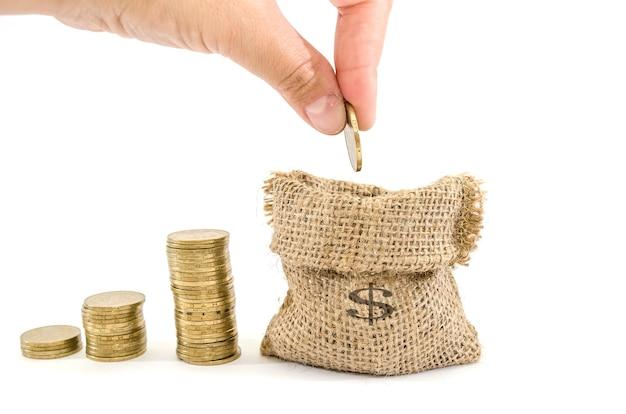 Ręka wkłada monetę do torby z pieniędzmi