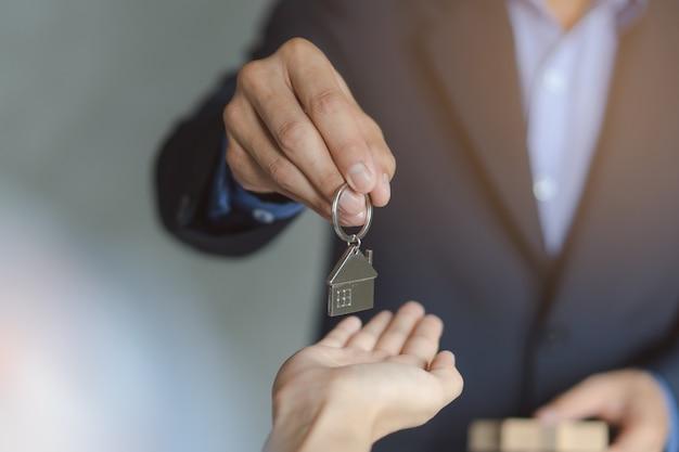 Ręka właściciela nieruchomości / właściciela dając klucz domu do kupującego / najemcy.