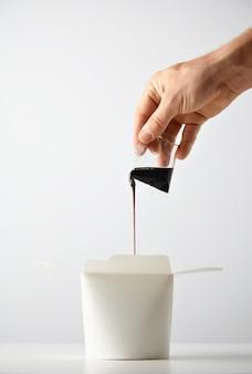 Ręka wlewa sos sojowy do otwartego pustego pudełka na wynos z wokiem, makaronem lub makaronem