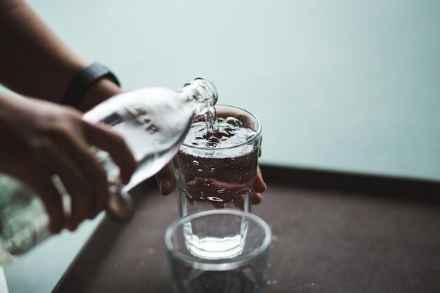 Ręka, wlewając wodę do szklanej butelki