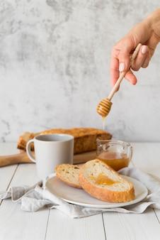 Ręka wlewająca miód na kromkę chleba