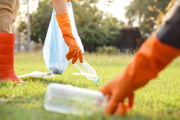 Ręka wolontariuszy zbiera śmieci, chłopak zbiera śmieci.