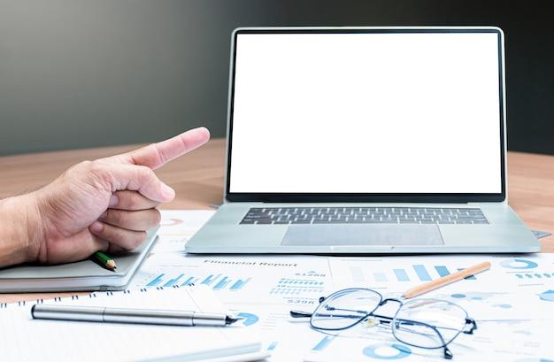 Ręka wskazująca palec, aby wyśmiewać prezentację pokazu slajdów podsumowania sprzedaży na wyświetlaczu laptopa z piórem, okularami i papierkową robotą na stole w sali konferencyjnej