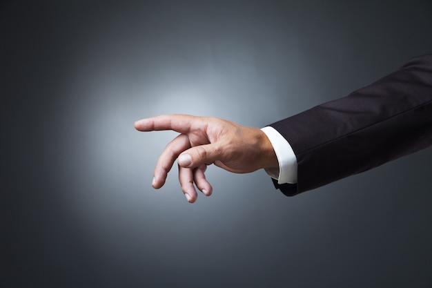 Ręka wskazująca symbol na ciemnym tle studia