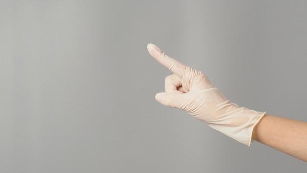 Ręka wskazuje i nosić rękawiczki medyczne na białym tle na szarym tle.