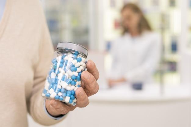 Ręka współczesnego starszego mężczyzny trzymającego butelkę z białymi i niebieskimi pigułkami lub biologicznie aktywnymi dodatkami przy zakupie leku w aptece