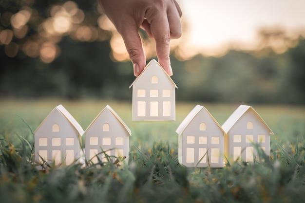 Ręka wybiera białego papieru domu modela od grupy dom na zielonej trawie.
