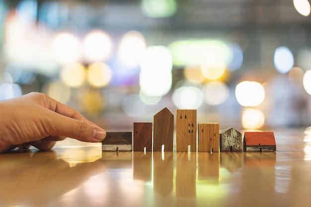 Ręka wybiera mini drewnianego domu modela od modela na drewno stole