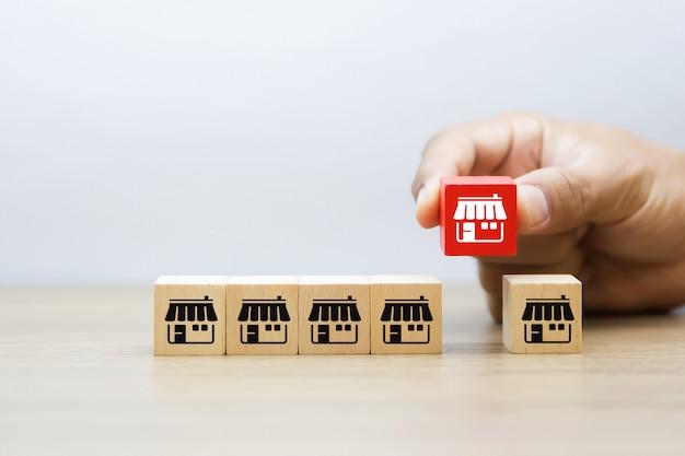 Ręka wybiera sklep z ikonami franczyzy na drewnianym blogu.