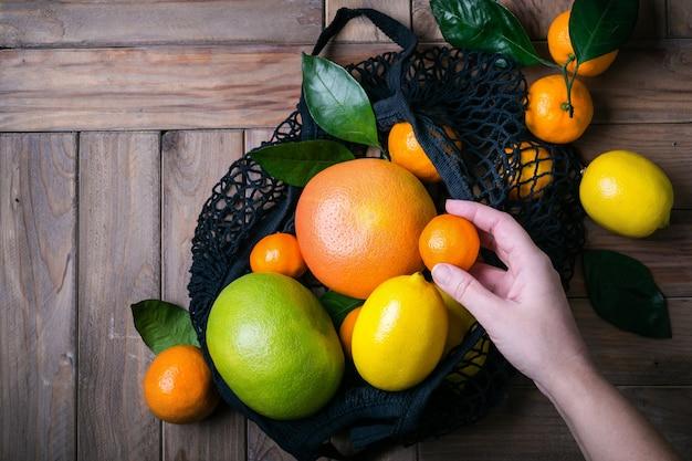 Ręka wyciąga owoce cytrusowe z torby z siatki tekstylnej. zdrowa żywność i koncepcja zero odpadów.