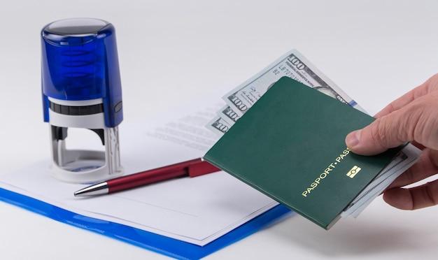 Ręka wyciąga zielony paszport z dolarami amerykańskimi na tle dokumentów i pieczątki