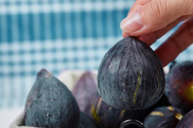 Ręka wyciągająca figę z kosza.