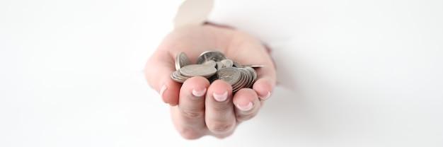 Ręka wyciągająca wiązkę monet z podartego papieru