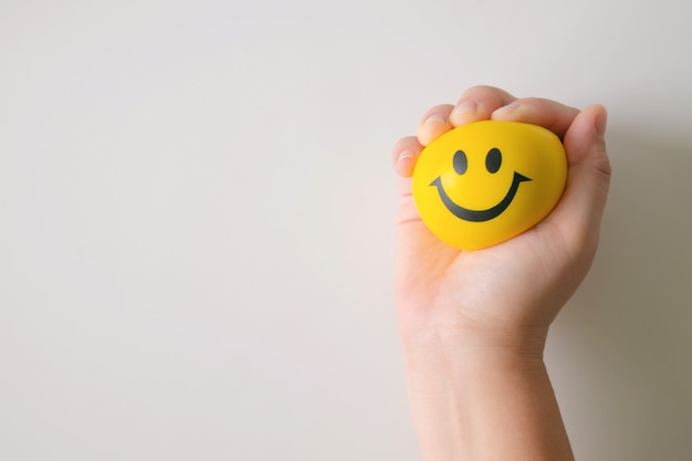 Ręka wycisnąć żółtą piłkę stres.