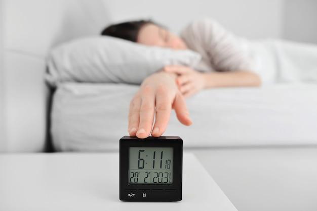 Ręka wyłącza budzik budząc się rano