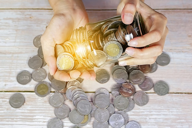 Ręka wylewająca monety ze szklanego słoika