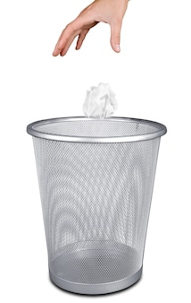 Ręka wyrzucająca papier do kosza na śmieci na białym tle