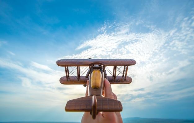 Ręka wystrzeliwuje drewniany samolot na tle błękitnego nieba