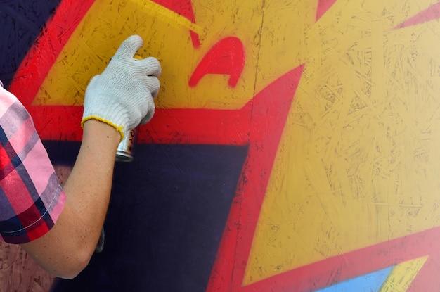Ręka z aerozolem, która rysuje nowe graffiti na ścianie.