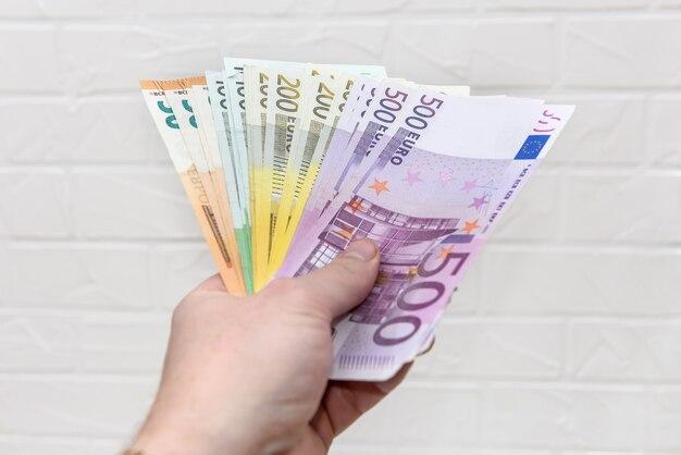 Ręka z banknotami euro na białej ścianie z cegły z bliska
