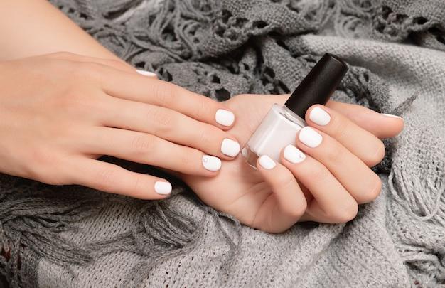 Ręka z białym wzorem do paznokci, trzymając butelkę z lakierem do paznokci.