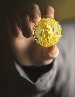Ręka z bitcoinem, fizyczny symbol zdjęcia z bliska kryptowaluty