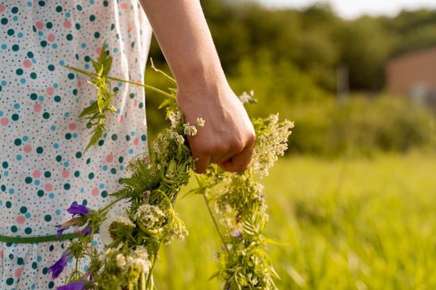 Ręka z bliska trzyma wieniec kwiatów