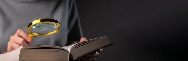 Ręka z bliska, trzymając lupę i książki lub podręcznik, szukając informacji. baner z miejsca na kopię