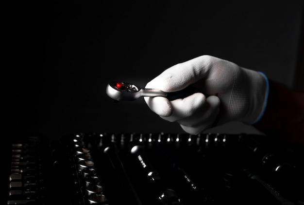 Ręka z bliska w białej rękawiczce z metalowym uchwytem zapadkowym ze stali nad zestawem narzędzi.