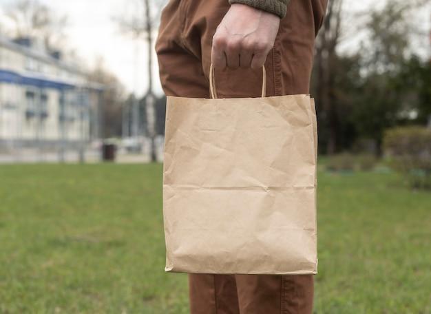 Ręka z brązowym opakowaniem rzemieślniczym lub pakietem w ręku na tle miasta i trawy.