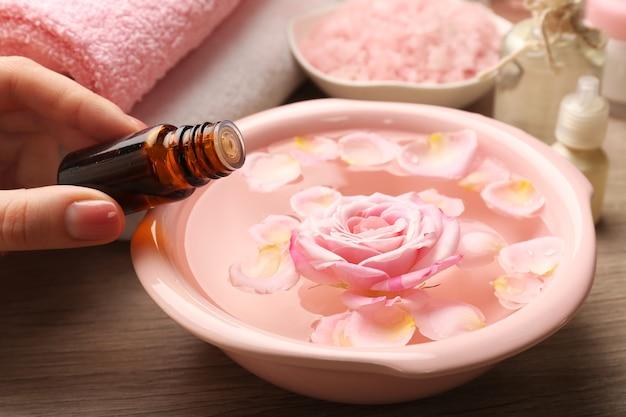Ręka z butelką esencji i miską wody spa z kwiatami na drewnianym stole, zbliżenie